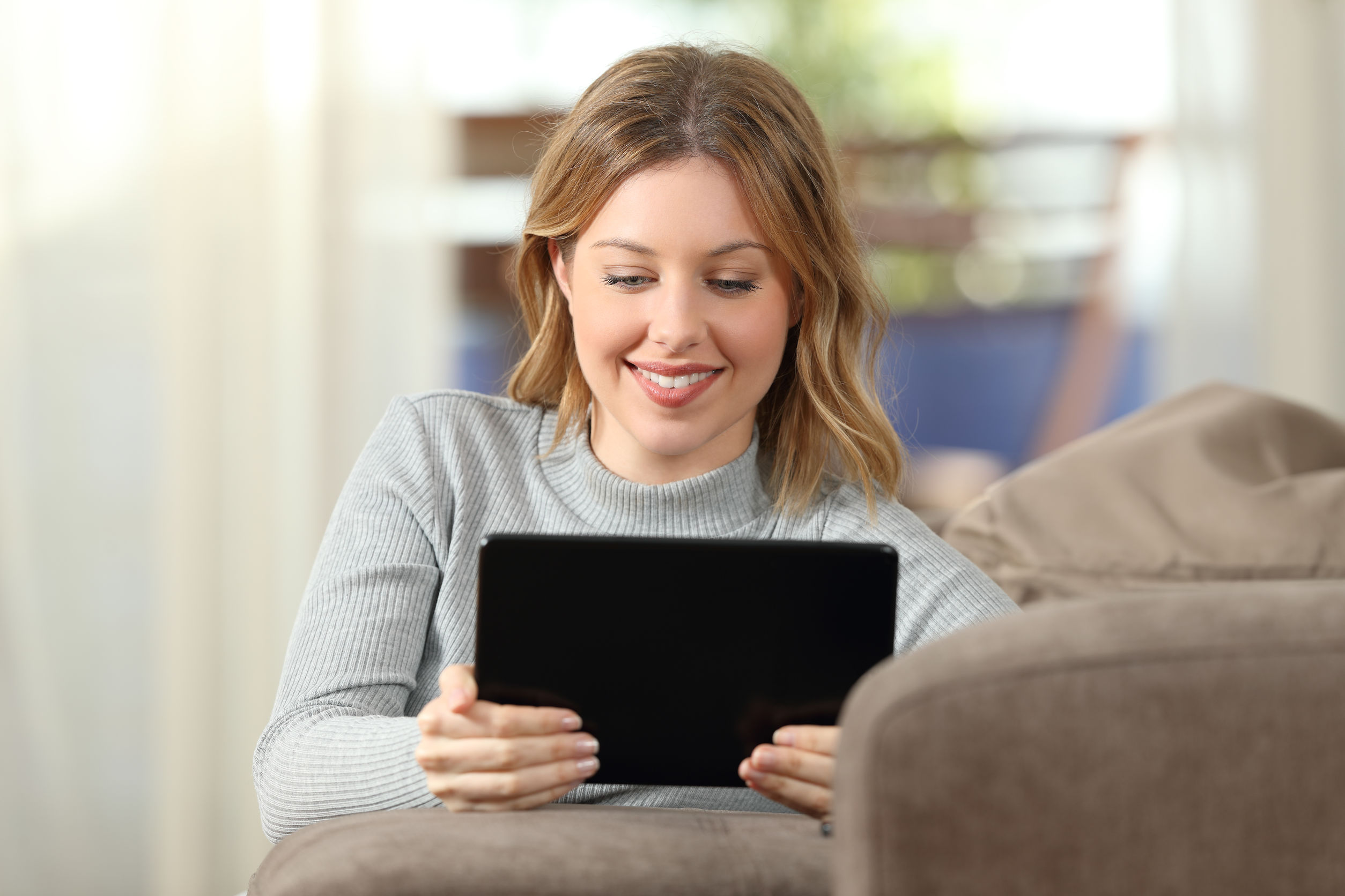 Front view of a woman watching video in a tablet sitting on a couch in the living room at home